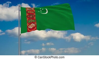 Flag of Turkmenistan against background of clouds floating on the blue sky