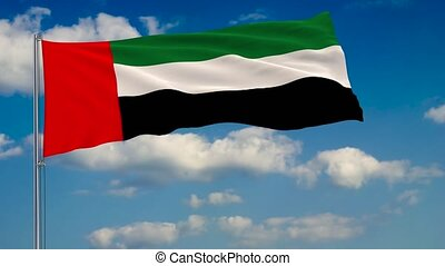 Flag of United Arab Emirates against background of clouds floating on the blue sky