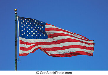 Flag of United States of America waving on the wind on blue sky background