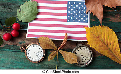 flag of usa, autumn season concept, laptop, clock, leaves, apple on wood background,image