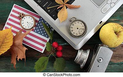 flag of usa, autumn season concept, laptop, clock, leaves, apple on wood background