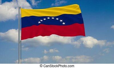 Flag of Venezuela against background of clouds floating on...