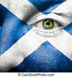 Flag painted on face with green eye to show Scotland support