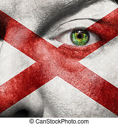 Flag painted on face with green eye to show Alabama support