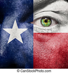 Flag painted on face with green eye to show Texas support