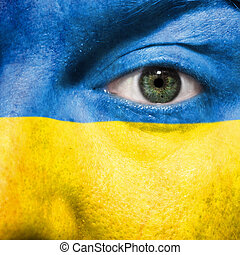 Flag painted on face with green eye to show Ukraine support in sport matches