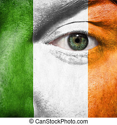Flag painted on face with green eye to show Ireland support in sport matches