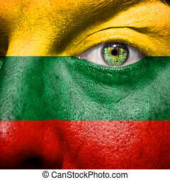 Flag painted on face with green eye to show Lithuania support