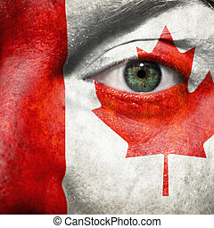 Flag painted on face with green eye to show Canada support in sport matches
