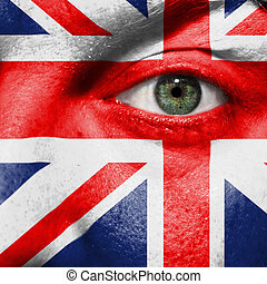 Flag painted on face with green eye to show UK support in sport matches