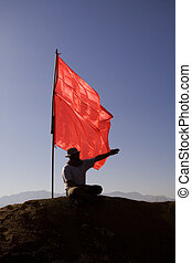 Flag - man pushing a red flag into the ground