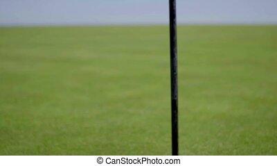 Flag pole next to hole on golf course - Close up on single...