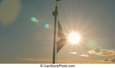 Flag silhouette flutters in the wind at sunset