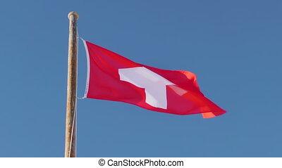 Switzerland flag in slow motion on blue sky