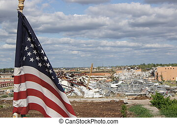 A American flag waiving with homes destroyed by tornado in joplin, Missouri in background