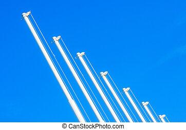 Flagpole with no flag on blue sky background.