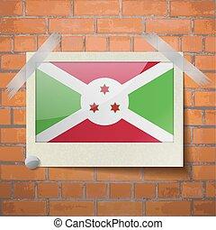 Flags Burundi scotch taped to a red brick wall