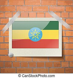 Flags Ethiopia scotch taped to a red brick wall