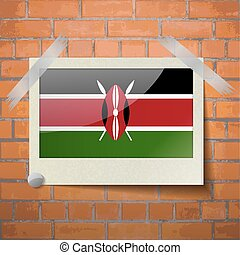 Flags Kenya scotch taped to a red brick wall