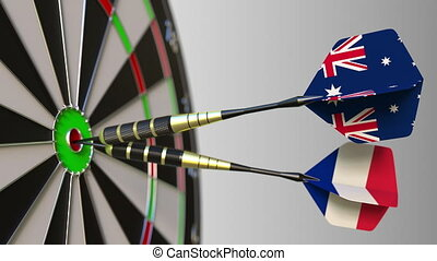 Flags of Australia and France on darts hitting bullseye of the target. International cooperation or competition animation