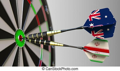 Flags of Australia and Iran on darts hitting bullseye of the target. International cooperation or competition animation