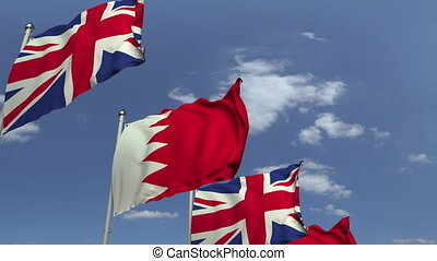 Flags of Bahrain and the United Kingdom against blue sky,...