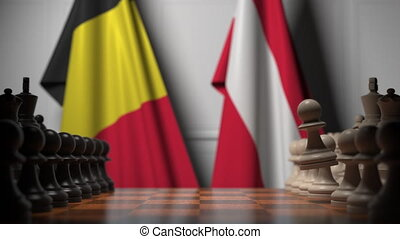 Flags of Belgium and Austria behind pawns on the chessboard. Chess game or political rivalry related 3D animation