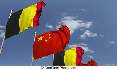 Flags of Belgium and China against blue sky, 3D rendering