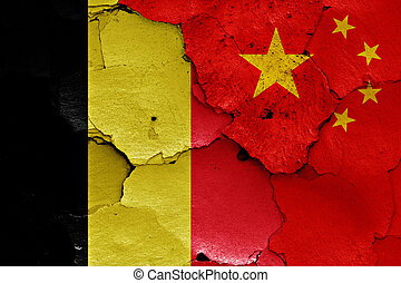 flags of Belgium and China painted on cracked wall