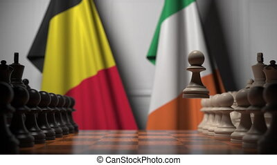 Flags of Belgium and Ireland behind pawns on the chessboard. Chess game or political rivalry related 3D animation