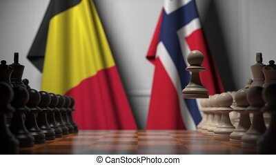 Flags of Belgium and Norway behind pawns on the chessboard. Chess game or political rivalry related 3D animation