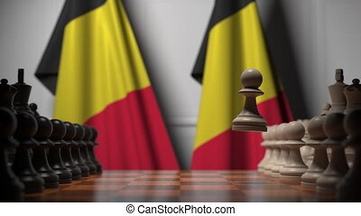 Flags of Belgium behind pawns on the chessboard. Chess game or political rivalry related 3D animation