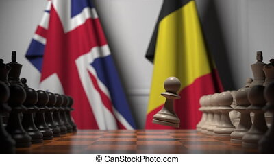 Flags of Britain and Belgium behind pawns on the chessboard. Chess game or political rivalry related 3D animation