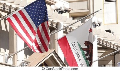 Flags of California and United States waving on flagpole in Gaslamp, center quarter of San Diego. Bear emblem of Republic and Star-Spangled Banner on flagstaff. Symbol of ptriotism and government.