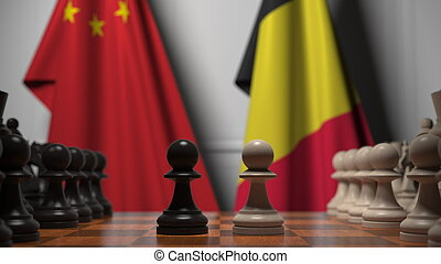 Flags of China and Belgium behind pawns on the chessboard. Chess game or political rivalry related 3D rendering