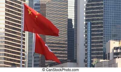 Flags of China and Hong Kong flying in the wind - National...