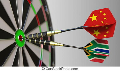 Flags of China and South Africa on darts hitting bullseye of...