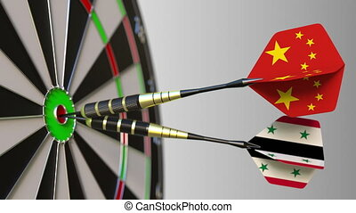 Flags of China and Syria on darts hitting bullseye of the...