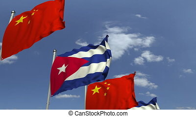 Flags of Cuba and China against blue sky, loopable 3D...