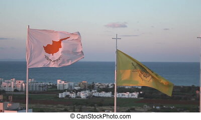 """Flags of Cyprus and Greek Orthodox Church waving in wind, seascape on background"""