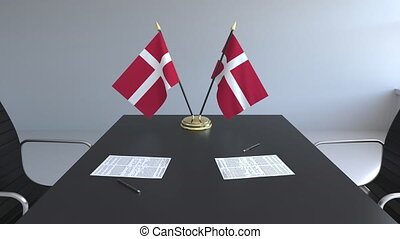 Flags of Denmark and papers on the table. Negotiations and...