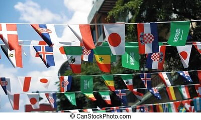Flags of different countries are hung in the air above the street. The world sports event concept