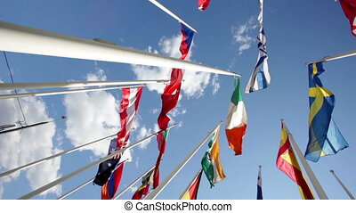 Flags of different countries flapping in sky - Many bright...
