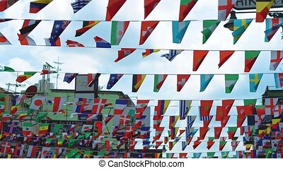 flags of different countries hang on the street