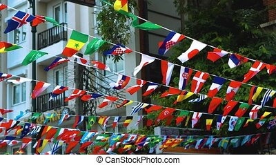 flags of different countries hang on the streets of the city