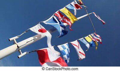 Flags of different countries on mast and ropes flapping in...
