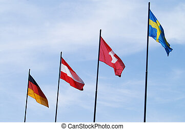 Flags of different countries on the blue sky