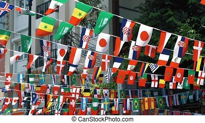Flags of different nations fluttering in the wind, slow motion. Symbols of the countries are suspended in the air
