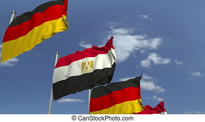 Flags of Egypt and Germany against blue sky, loopable 3D...