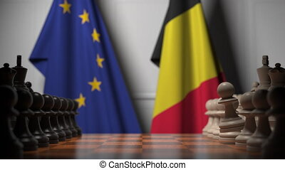 Flags of Eu and Belgium behind pawns on the chessboard. Chess game or political rivalry related 3D animation